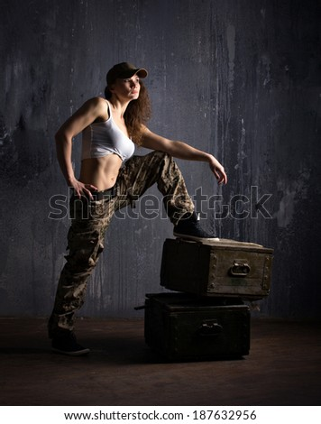 adult girl in camouflage clothes standing on military boxes on dark grunge wall background - stock photo