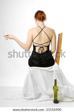 Adult girl sits and holds glass with wine on light background, empty bottle near chair, back naked - stock photo