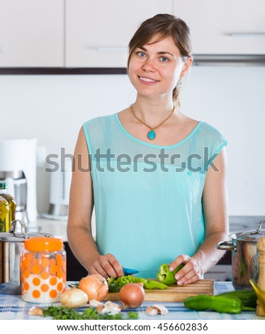 Adult girl standing at a kitchen table with casserole and vegetables