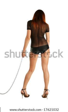 Adult girl standing back in black short catsuit , shoulders lowered, edge of long metal chain in her left hand, legs placed inwards on high heels - stock photo