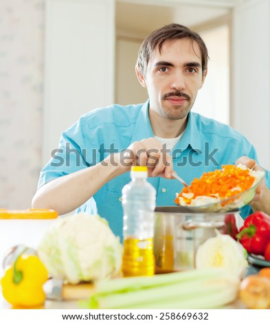 Adult guy cooking dinner with vegetables at home kitchen - stock photo