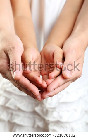 Adult hands holding kid hands