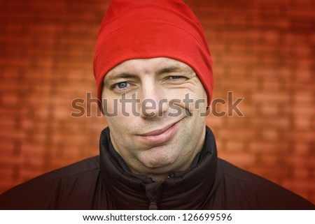 adult handsome man in red hat winking - stock photo