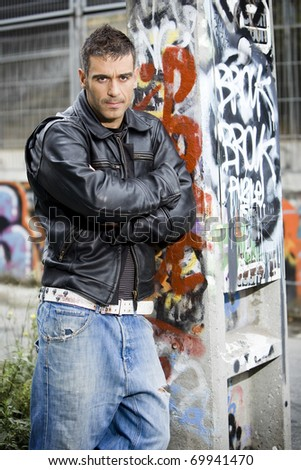 adult handsome man posing outdoors in a graffiti wall background