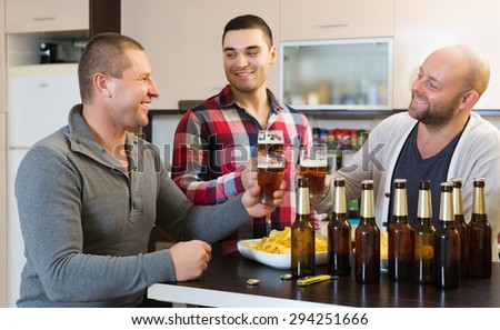 Adult happy friends relaxing with beer and smiling at home - stock photo
