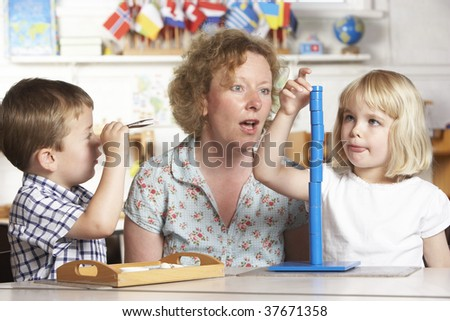 Adult Helping Two Young Children at Montessori/Pre-School - stock photo