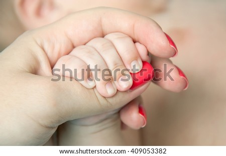 Adult holding a new born baby hand