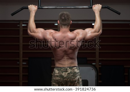 Adult Male Athlete Doing Pull Ups - Chin-Ups In The Gym - Best Exercise For Back - stock photo