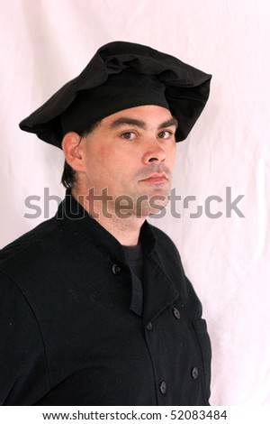 adult male chef in black uniform looking directly at viewer with head slightly turned and standing at attention