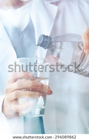 Adult male doctor showing glass to water