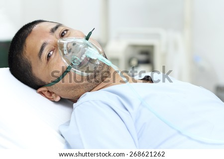Adult male patient in the hospital with oxygen mask. - stock photo