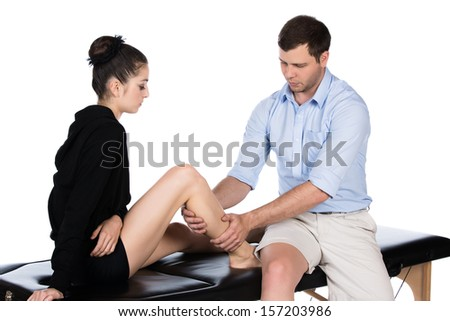 Adult male physiotherapist treating the foot of a female patient. Patient is sitting on a bed. - stock photo