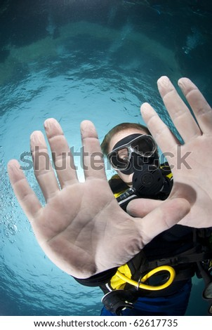 Adult male scuba diver showing the palms of his hands underwater. Focus on the divers' face. Ras Ghozlani, Sharm el Sheikh, Red Sea, Egypt.