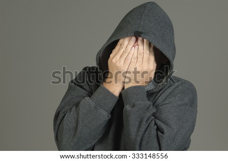 Adult male unidentified hides face with despair - stock photo