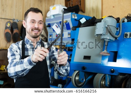 Adult male worker sharpening tools for fixing in shoe repair workshop