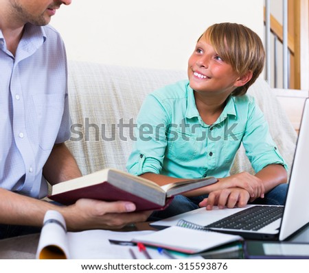 Adult man and teenager boy studying with laptop indoors  - stock photo