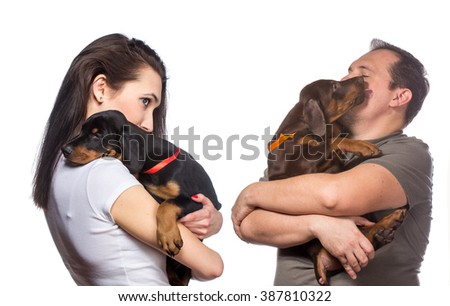 Adult man and woman holds her sweet doberman puppies, isolated on white background - stock photo