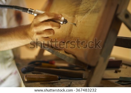 Adult man at work as artist, chiselling a bas-relief in his atelier. He works with a drill to ceasel a wood painting.  - stock photo