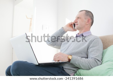 Adult man calling by smartphone at home - stock photo