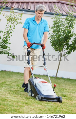Adult man cutting grass in his garden yard with lawn mower