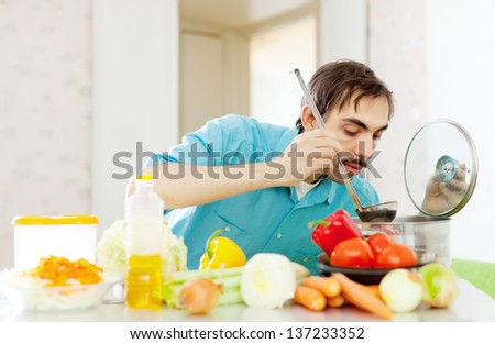 Adult man doing veggy lunch at kitchen - stock photo