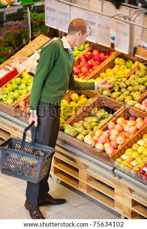 Adult man examining fruits to buy in shopping centre - stock photo