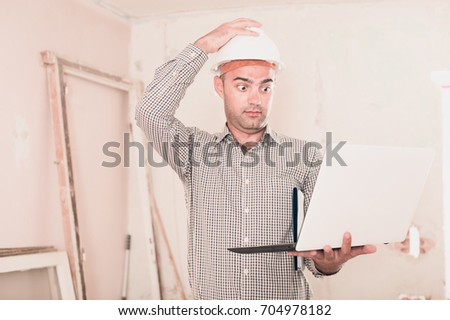 Adult man headman surprised and working with laptop in helmet indoors