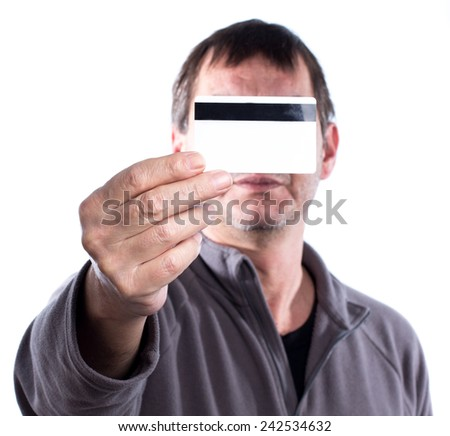 Adult man holding a credit card in front oh his face - stock photo