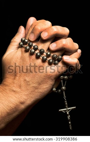 Adult man holding rosary in his hands