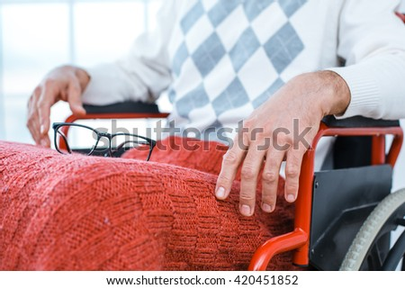 Adult man in wheelchair. Close up photo of man with glasses sitting in wheelchair - stock photo
