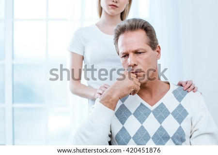 Adult man in wheelchair. White interior with big window. Sad man and young helper - stock photo