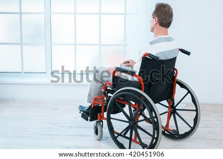 Adult man in wheelchair. White interior with big window. Sad man looking at window. Back view photo - stock photo