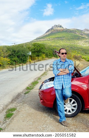 Adult man is standing near his broken car waiting for tow - stock photo