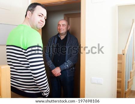 Adult man opening  door his neighbor - stock photo