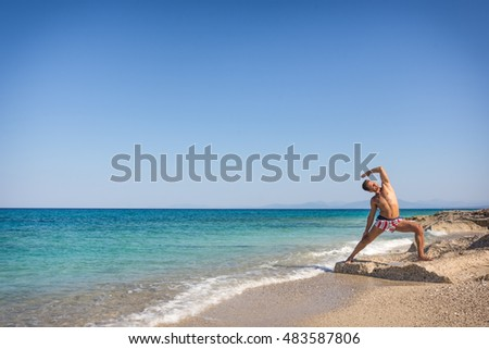 Adult man practicing yoga on the beach in Greece, in position reverse warrior