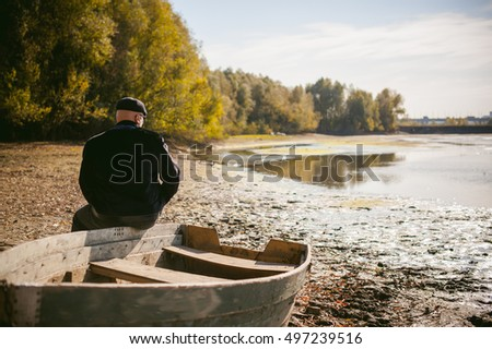adult man sitting on an old wooden boat and looks into the distance