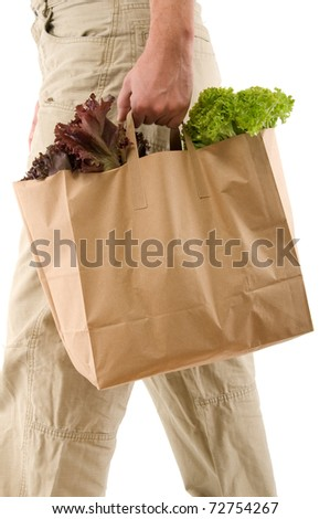 Adult man walking with paper bag full of groceries isolated on white background. - stock photo