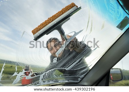 Adult man washing dirty windshield of his car.  - stock photo