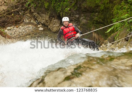 ADULT MAN WEARING WATERPROOF EQUIPMENT DESCENDING A WATERFALL