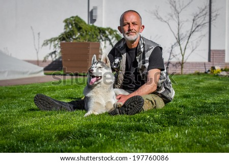 adult man with a dog in the yard - stock photo
