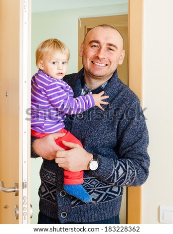 Adult man with daughter opening  door of his apartment - stock photo
