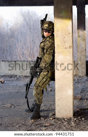 Adult man with rifle and gun hiding behind the column