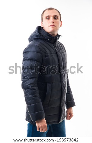Adult man with winter clothes standing on white background. Man stands in a winter jacket isolated on white background. Casual cool young guy. Attractive guy in winter clothes. - stock photo