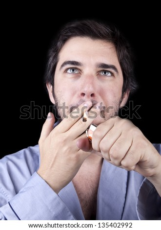 Adult man (30 years old), which  appears to be quite a bum wearing a light blue fabric robe, gazing upwards, concentrated in igniting a marijuana spliff (reefer; joint). Isolated on black background. - stock photo