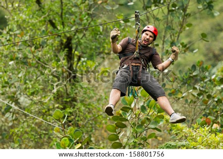 Adult man, zip line adventure in Ecuadorian rainforest. - stock photo