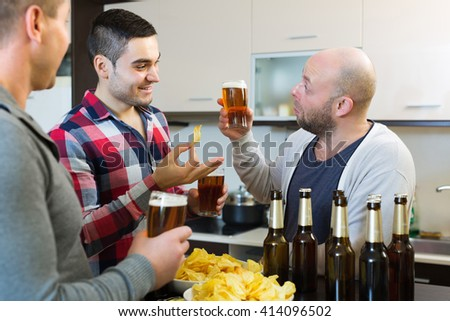 Adult men relaxing with beer and smiling at home - stock photo