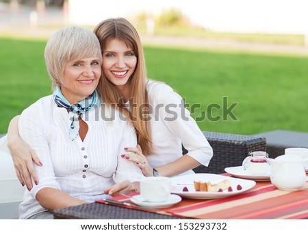 adult mother and daughter drinking tea or coffee and talking outdoors  - stock photo