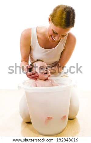 Adult mother wearing bright casual clothes, she kneels on the floor and bathes her newborn baby in the bath bucket. Carefully, she keeps the baby's head. Isolated against white background. - stock photo