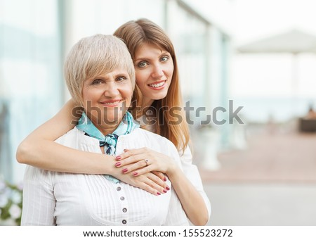 Adult mother with her daughter hugging - stock photo