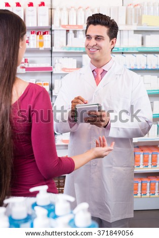 adult  pharmacist serving young woman in pharmacy and smiling - stock photo